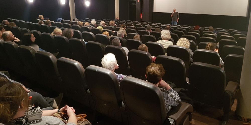Kinosaal mit Redner und Publikum